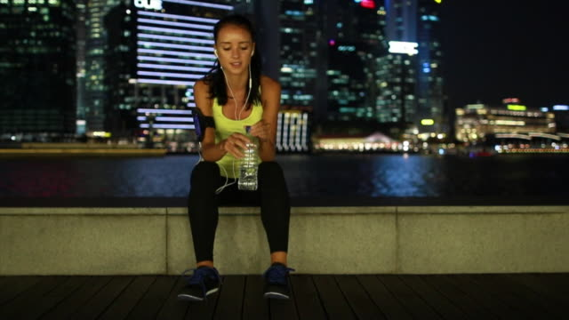 WS Young woman resting after drinking water after a work out.