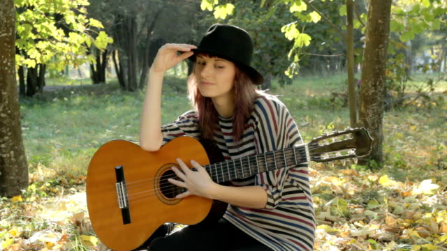 Young woman resting in park, holding guitar, smiling, posing outdoors.