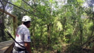 Young woman rides zipline in Belize