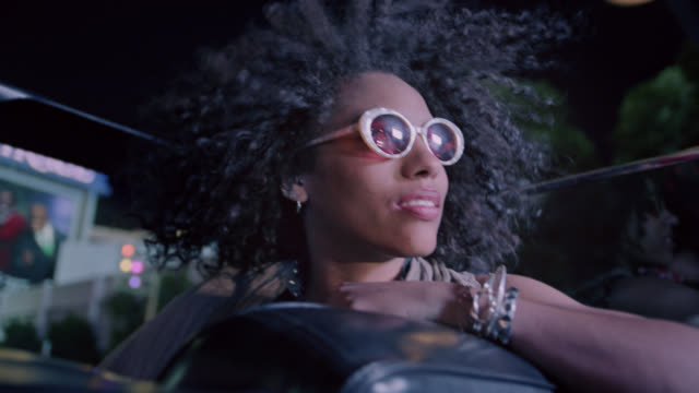 Young woman riding in classic convertible gazes up at city lights at night.