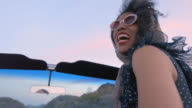 POV. Young woman riding in classic convertible looks back and laughs on road trip with friends.