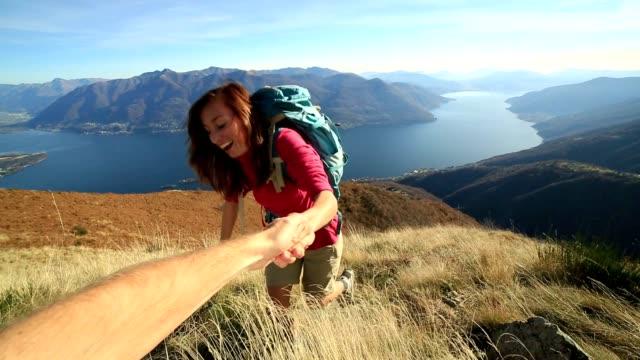 Young woman rock climbing, partner giving helping hand
