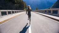 Young woman running in the middle of a road