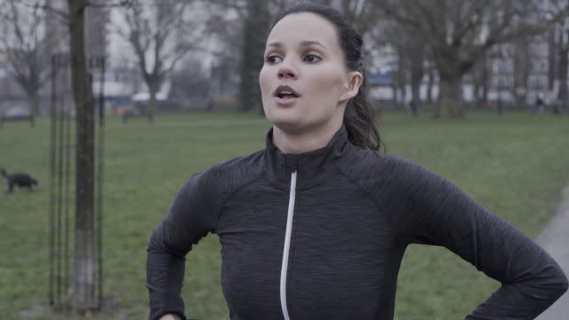 A young woman running in the park in winter.