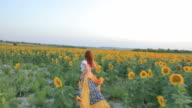 Young woman running sunflowers field sunset