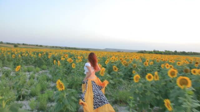 Young woman running sunflowers field sunset