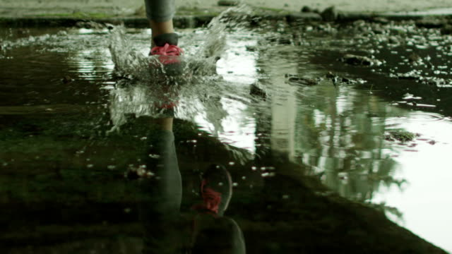 Young woman running through the water