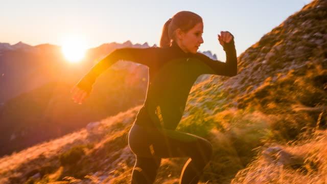 Jonge vrouw die de berg aangelopen bij zonsondergang