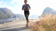 Young woman runs along lakeshore pathway in autumn
