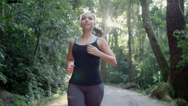 MS, TS A young woman runs on a forest road / Rio de Janeiro, Brazil