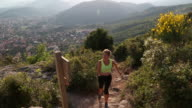 Young woman runs up trail above village, looks out over sea