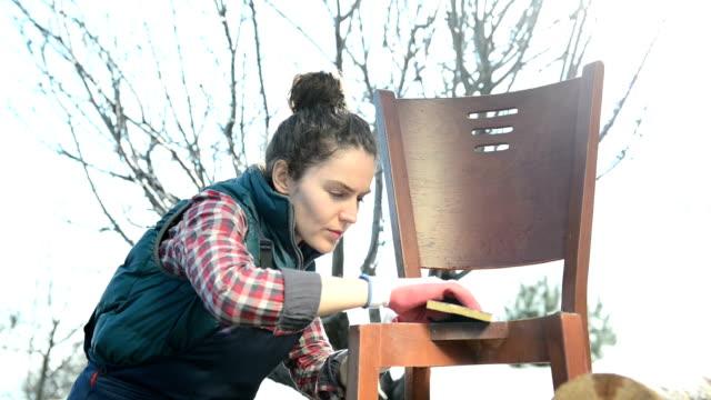 Jonge vrouw schuren van een oude stoel
