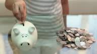 Young woman saving money into piggy bank, Delhi, India