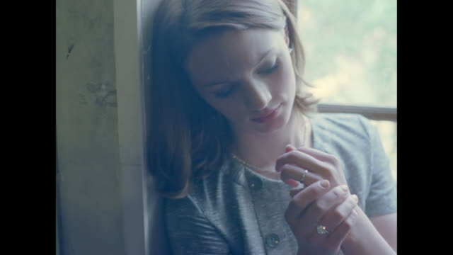 Young woman seemingly in love leaning up against a window frame.
