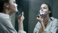 Young woman shaving her face