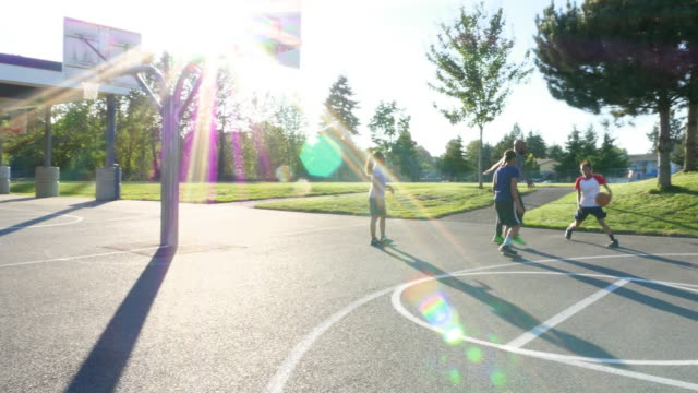 MS Young woman shooting jump shot on outdoor basketball court on summer evening while playing with father and sisters