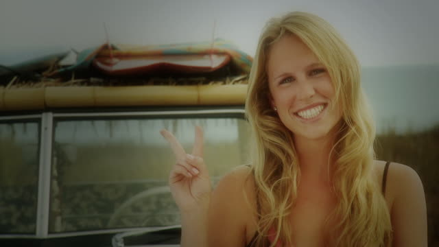 CU Young woman showing peace sign, surfboards on roof rack of jeep in background / Laguna Beach, California, USA