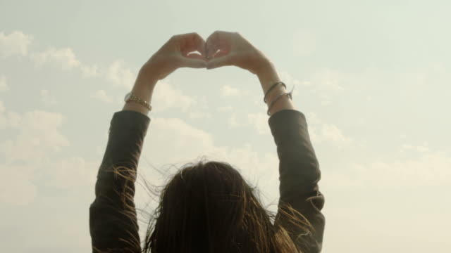 A young woman shows her love raising her arm forming a heart.