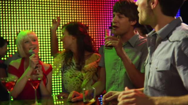 MS SLO MO Young woman singing karaoke with friends in nightclub / London, UK