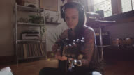 MS SLO MO. Young woman sings and plays acoustic guitar in sunny apartment studio.