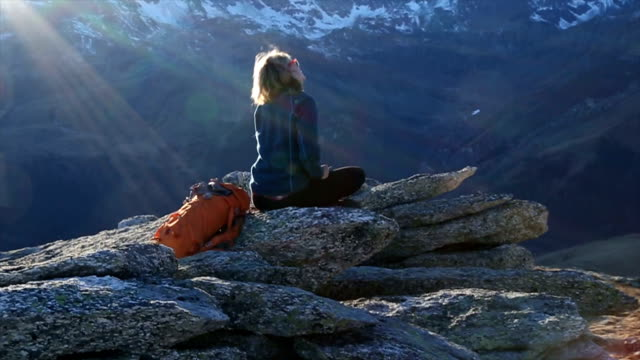 Young woman sits on boulder overlooking mountain panorama