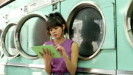 MS A Young Woman sits waiting in a Launderette
