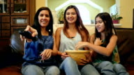 Young woman sits with mother and preteen sister to watch movie and eat popcorn