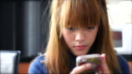 Young woman sitting and using mobile phone