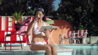 MS Young woman sitting at edge of pool and reading on ipad / Santa Monica, CA, United States