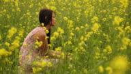 Young woman sitting in the mustard field, Haryana, India