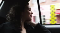 CU Young woman sitting on backseat of car and smiling / New York City, New York, USA