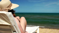Young woman sitting on deck chair on the beach