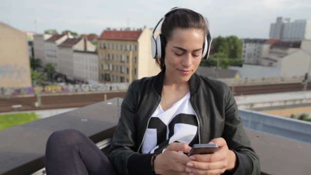 Young woman sitting on rooftop in Berlin, Germany listening to music with headphones.