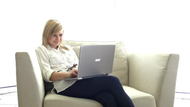 Young woman sitting on sofa, using laptop