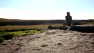 Young woman sitting on the cliff edge in Iceland