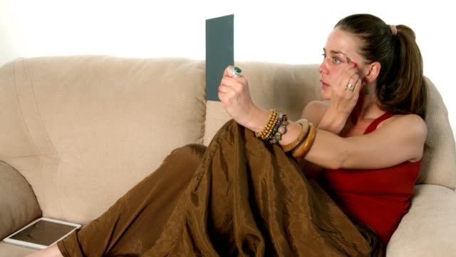 Jonge vrouw zittend op de Bank pincet, plukken, trekt of knijpen van haar wenkbrauwen