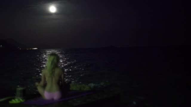 Ung kvinna som sitter på stranden. Full moon.