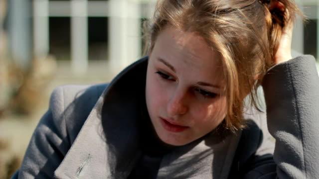 Junge Frau sitzt allein im Freien, der sich sehr verärgert, Gekränktheit und Weinen