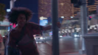 Young woman skips and swings around street light on Las Vegas strip at night.