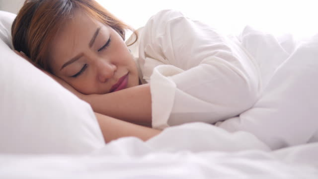 4K : Young woman sleeping in bed