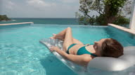 MS Young woman sleeping on inflatable raft in infinity pool with ocean in background/ Scarborough, Tobago, Trinidad and Tobago