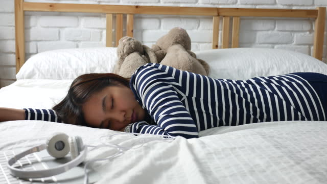 Young woman sleeping on the bed with headphones