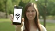 Young woman smart phone with wifi in the park