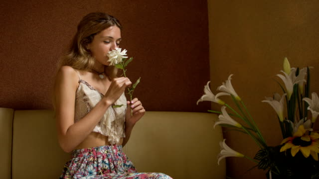 Young woman smelling a flower at home