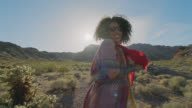 SLO MO. Young woman smiles and poses for camera with flowing red scarf in Nevada desert.