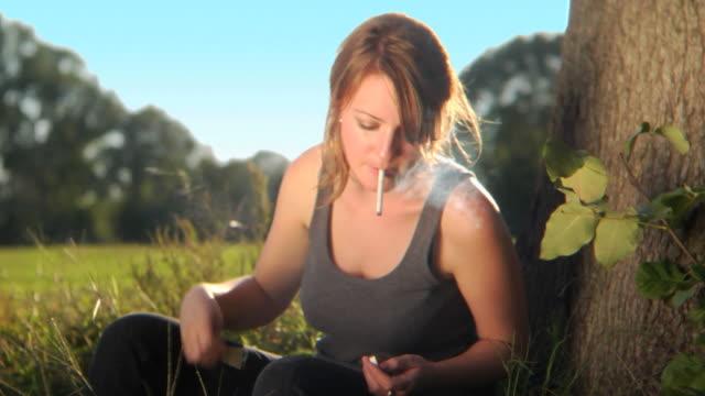 HD CRANE: Young woman smoking cigarette