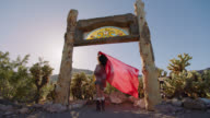 SLO MO. Young woman spreads a flowing red scarf in a rustic gateway surrounded by desert cacti.