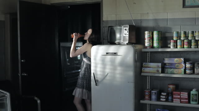 MS Young woman standing backwards leaned on fridge, drinking some bevereage in a sexy manner / Palmdale, CA, United States