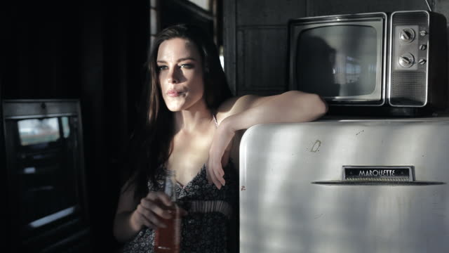 MS Young woman standing backwards leaned on fridge, drinking some bevereage in sexy manner / Palmdale, CA, United States