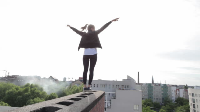 Young woman standing on rooftop in Berlin, Germany.